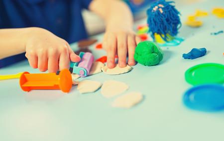 테이블에 plasticine에서 아이 곰 팡이. Plasticine와 손입니다.