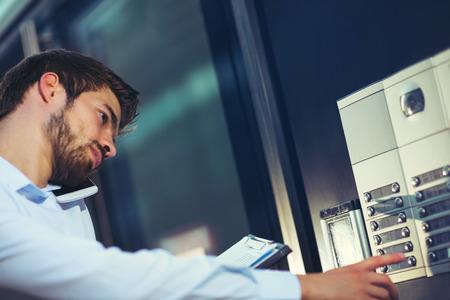 Het portret van een jonge gelukkige zakenman buiten het bureaugebouw gaat het gebouw in Stockfoto