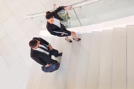 Due uomini d'affari che parlano mentre camminano in ufficio Archivio Fotografico