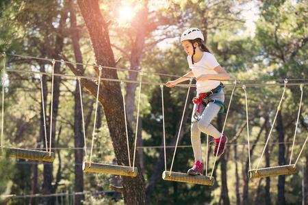 Gelukkig schoolmeisje die van activiteit in een het beklimmen avonturenpark op een de zomerdag genieten