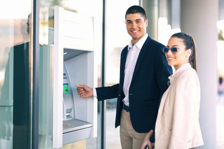 Junge Leute mit Kreditkarte stehen neben dem Geldautomaten, um Geld zurückzuziehen Standard-Bild - 74206231