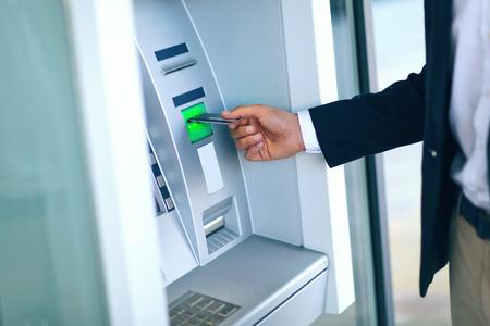 Close-up van Persoon die Creditcard gebruiken om Geld van ATM-Machine terug te trekken
