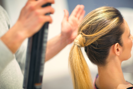 Young woman with blonde hair made by  hair stylist in beauty salon Stock Photo