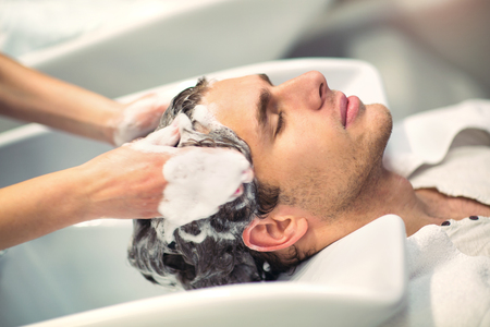 Hairdresser washing hair to her handsome client. Barber at work. Man at barbershop. Stock Photo