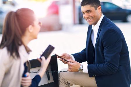 Couple assis sur un banc solaire et téléphone frais Banque d'images - 75465699