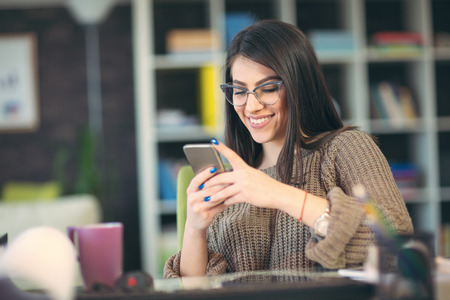 Woman sitting in home office at desk and holding smart phone