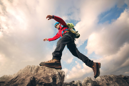 Mountaineer jumps over rocks in mountin
