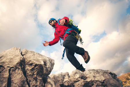 mountin: Mountaineer jumps over rocks in mountin, cloudy weather Stock Photo