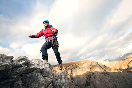 mountin: Mountaineer jumps over rocks in mountin cloudy weather Stock Photo