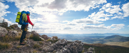 Panoramic photo of mountaineers standing with backpack on top of a mountain and enjoying the view Фото со стока
