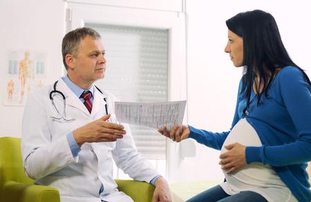임신 한 여자는 병원에 앉아있는 동안 문서를 들고 남성 의사의 초상화
