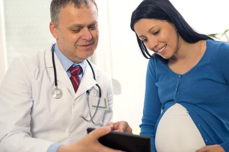 병원에서 임신 한 여자에 게 디지털 태블릿에 초음파 이미지를 보여주는 부인과 의사