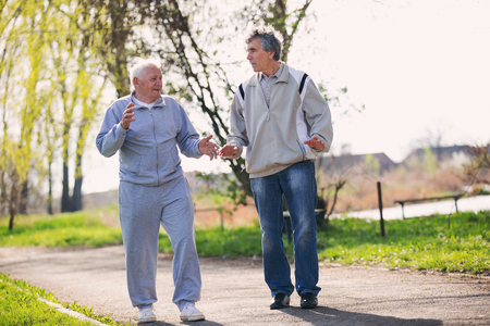 frailty: Adult son walking with his senior father in the park. Stock Photo