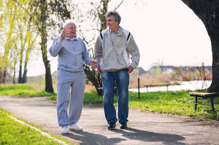 Adult son walking with his senior father in the park. Stock Photo