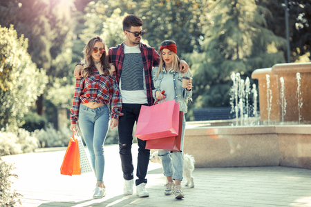 Three friends holding colored bags in hand on the way to the Mall for shopping Stock Photo