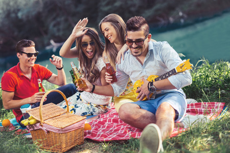 river: Young people having picnic near the river. Young friends relaxing by the river Stock Photo