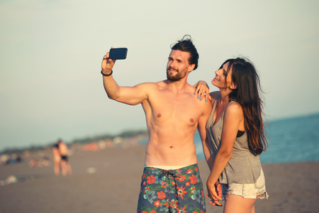 Couple walking on beach at sunset taking selfie picture on mobile phone relaxing together