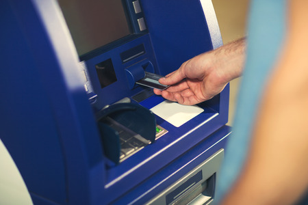 withdrawing: Man uses an ATM card inserted into the ATM machine for cash.