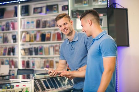Dos hombres jóvenes eligiendo teléfonos inteligentes en la tienda sonriendo Foto de archivo