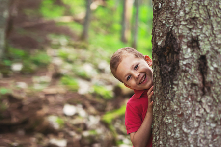 Young boy hugging a tree in the forest