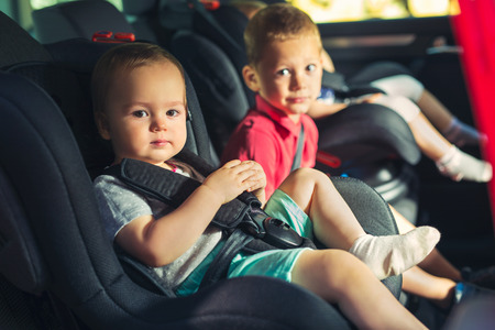 Three children in car safety seat - family, transport, safety, road trip and people concept Stock Photo
