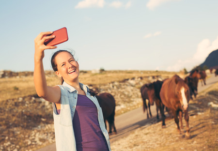 Taking selfie in nature. Girl make selfi with a smartphone in nature, in the background is the herd of wild horses