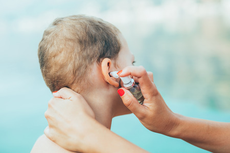 Mother treating little boy ear infection by the sea