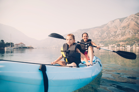 Mother and son kayaking at the sea Stock Photo