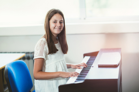 Beautiful girl playing the piano at the music school selective focus Stock Photo
