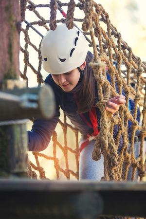 Happy school girl enjoying activity in a climbing adventure park on a sunny day