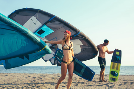 Pretty smiling Caucasian woman and man kitesurfer walking on the beach with their kite