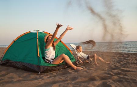 Strandcamping. Kinderen kamperen en activiteiten op het strand bij zonsondergang
