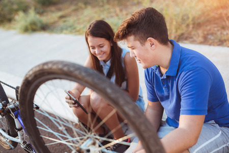 self sufficient: Teenager boy repair tire on bicycle , female friend sitting next to him, using digital tablet for instructions, summer outdoor photo Stock Photo