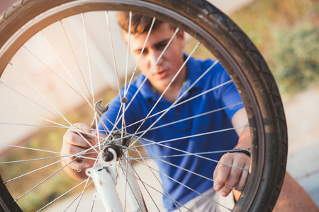self sufficient: Teenager boy repair tire on bicycle summer outdoor photo Stock Photo