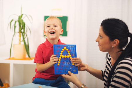 Little boy during lesson with his speech therapist. Learning through fun and play Reklamní fotografie