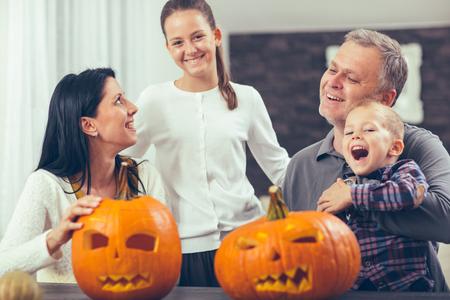 Family carving big orange pumpkin for Halloween and having fun