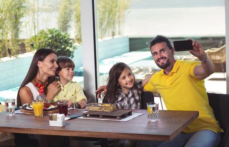 A four-member family having great time in a restaurant, make selfie photo Stock fotó