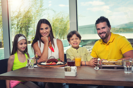 A four-member family having great time in a restaurant Stock fotó
