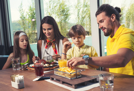 A four-member family having great time in a restaurant Banco de Imagens