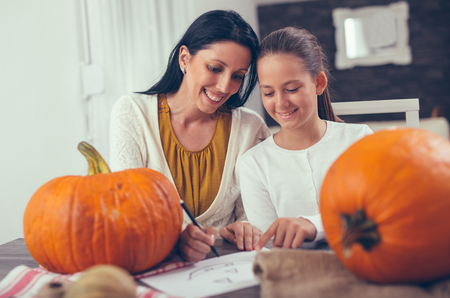 Mother with daughter creating big orange pumpkin for Halloween and having fun