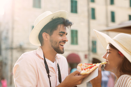 Happy couple in love sharing pizza on street
