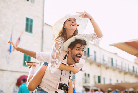 Man giving a piggyback ride to his girlfriend. Happiness lifestyle and tourism concepts