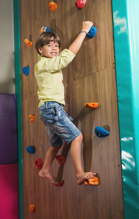 Little Boy Climbing a Rock Wall Indoor. Childrens Entertainment Sports Soft Ground.