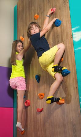 Children Climbing a Rock Wall Indoor. Childrens Entertainment Sports Soft Ground.
