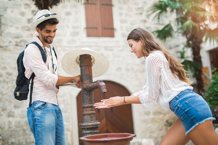 Young couple of tourist near a drinking fountain with water 版權商用圖片 - 86369860