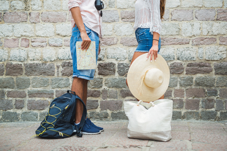 Unrecognizable tourist man and woman with backpack and map standing.