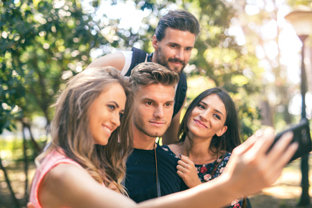 Group of four funny friends taking selfie with a smart phone in summer park