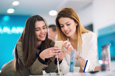 Two women is holding a mobile phone in store. They are looking for new smart phone.