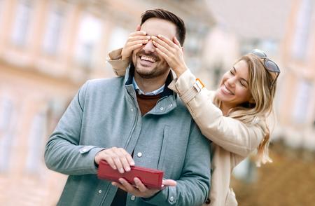 Frau überraschend seinen Freund mit einem Geschenk. Junge Frau mit dem giftbox, der seine Freundaugen schließt, um eine Überraschung für ihn zu machen. Standard-Bild - 87919741