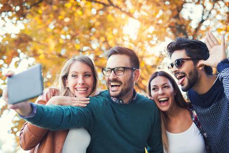 Grupo de cuatro amigos divertidos tomando selfie con un teléfono inteligente en el parque